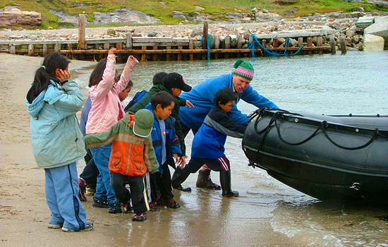 A group of children help push a Zodiac into the water