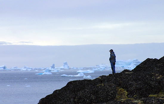 A man stands on a cliff and looks out over the icebergs in Hudson Bay