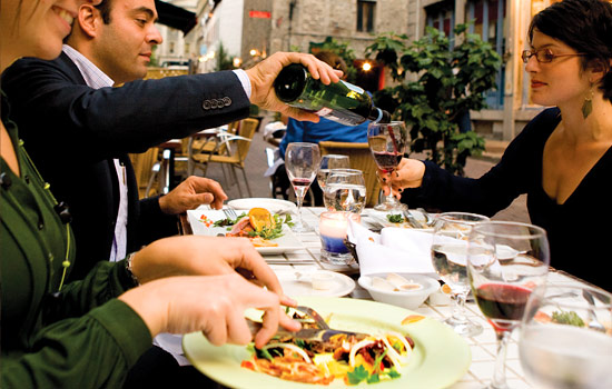 Friends dine on French cuisine and red wine in Quebec