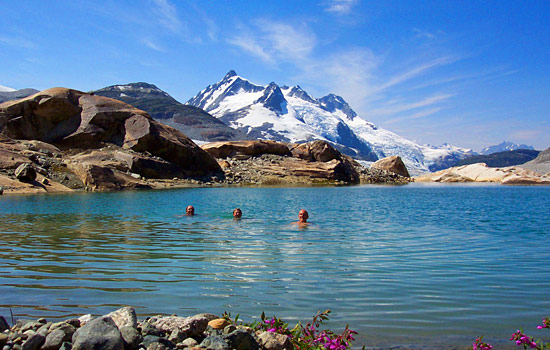 Three people take a swim in an alpine lake