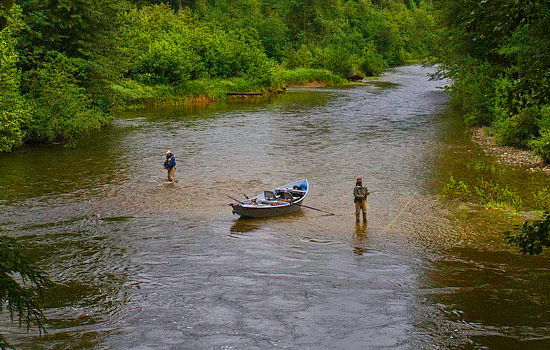 Two men fly fishing in a river with a row boat