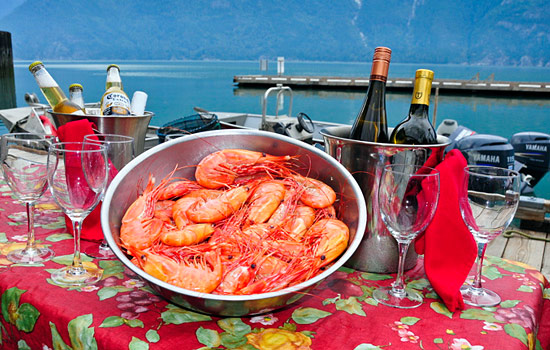 A table is laid out with wine, beer and fresh prawns over looking a lake in Bella Coola