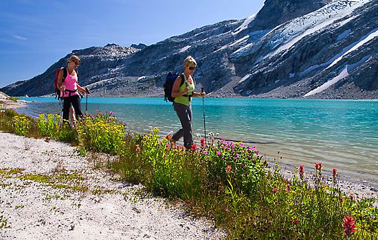 Two hikers are dwarfed by the surrounding Rocky Mountains on the alpine trails