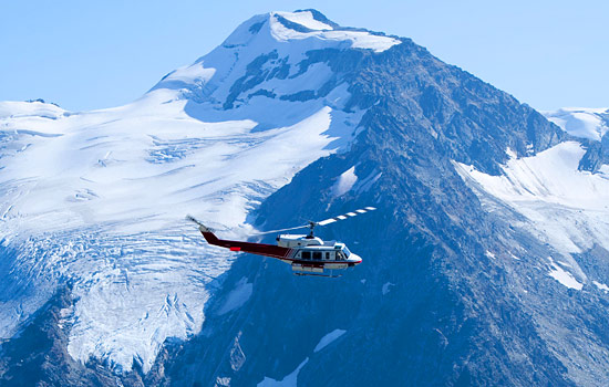 A helicopter flies past snow capped mountains in the Bugaboo National Park