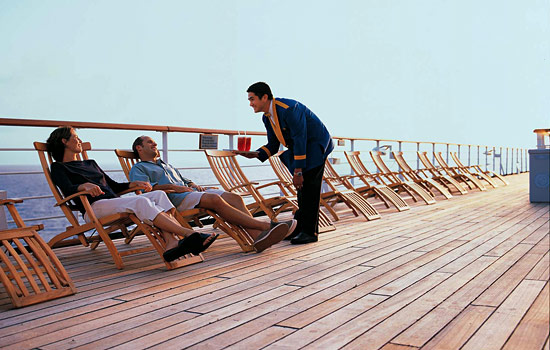 Couple enjoy drinks service on deck of the Holland America MS Noordam