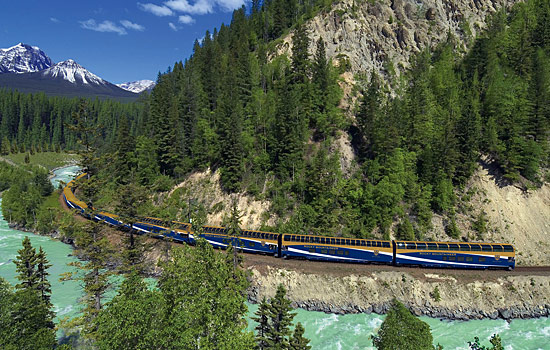 The Rocky Mountaineer travels beside a river and mountains