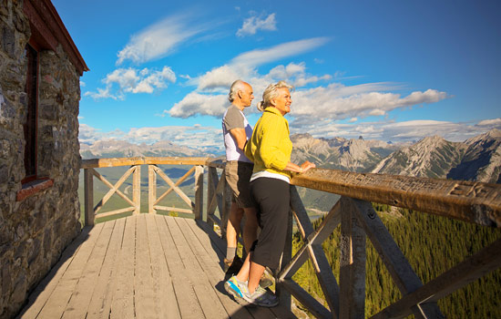 A couple look out over the Rockies from a viewpoint