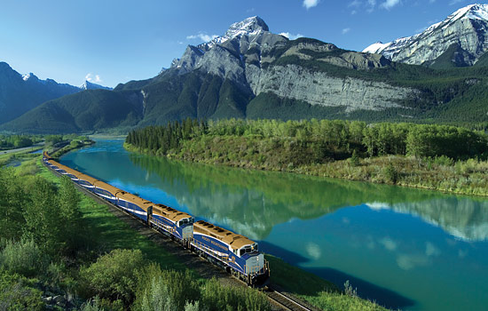 View of the Rocky Mountaineer travelling by a river with the Rockies towering above