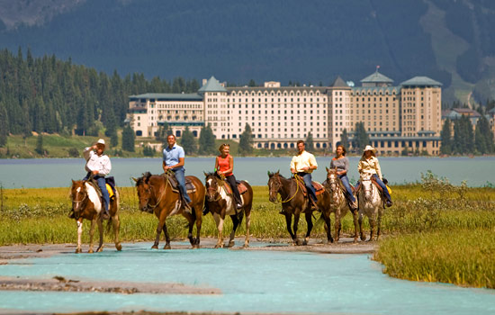 A small group tour head out on a guided horseback ride at Lake Louise