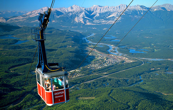 Passengers ride the Jasper Tramway high above Jasper National Park with views of the Rocky Mountains, lakes and endless forest below