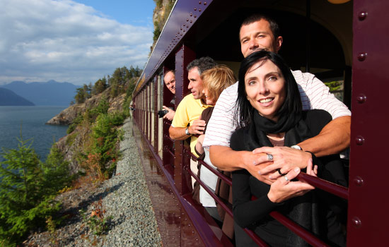 Rocky Mountaineer passengers take in the passing scenery on the Sea to Sky to Whistler