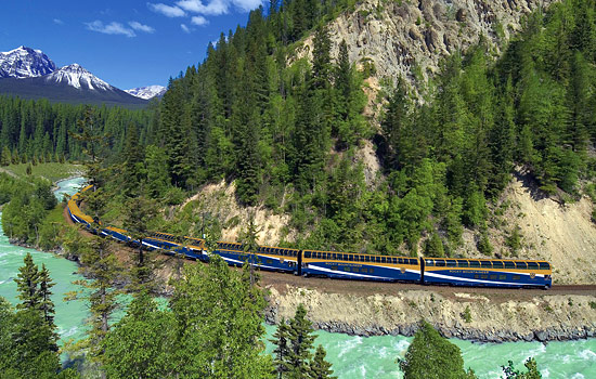 The Rocky Mountaineer train travels around a mountain past a river enroute to Vancouver