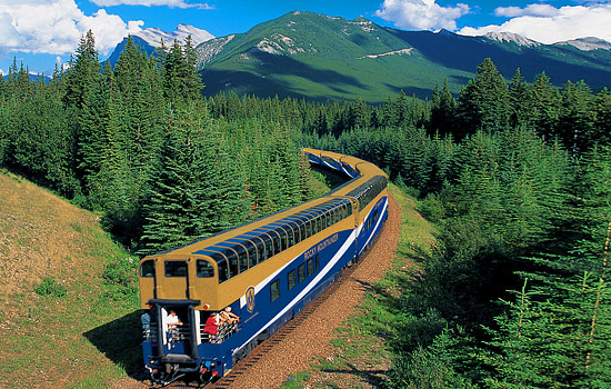 The Rocky Mountaineer winds through mountains as passengers enjoy the views from the front car