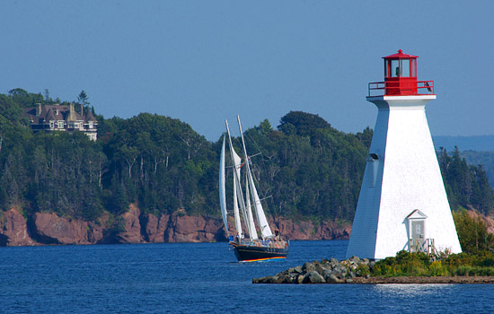 Sailboat passing a lighthouse in Nova Scotia