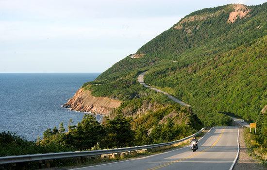 A motorcyclist rides along the winding coastal roads of Cape Breton