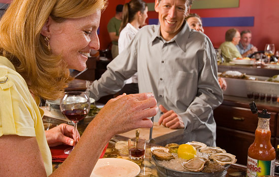 A woman enjoys local oysters in a lively restaurant in Nova Scotia