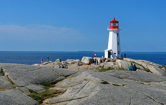 People gather at Peggy's Cove lighthouse to enjoy the coastal views