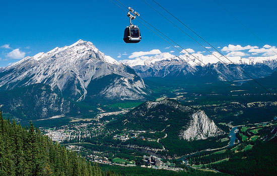 Gondola ride over Banff town with the Rocky mountains in the distance