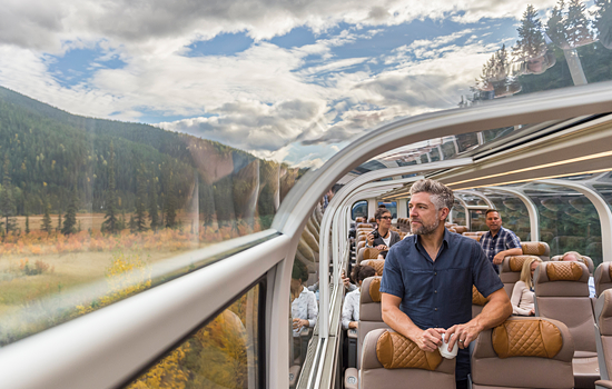 Passengers on the Rocky Mountaineer enjoy mountain views from the dome car