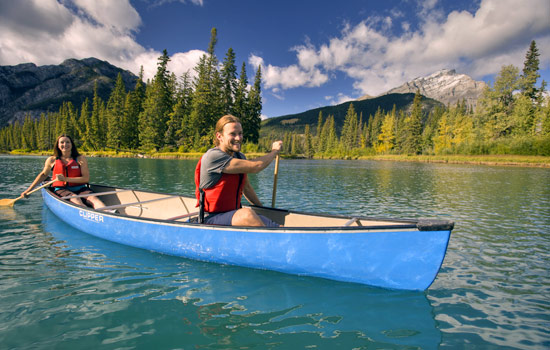 A couple paddle along the Bow River in a canoe