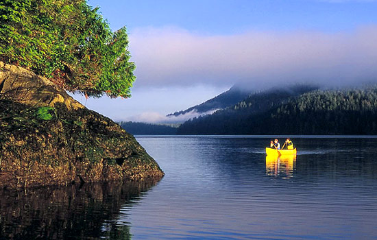 Two people canoe on a calm and serene lake