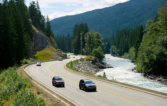 Drivers heading north along the Sea to Sky highway past mountains and a flowing river