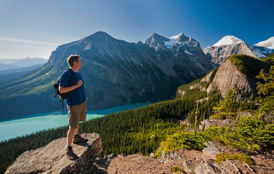 A hiker enjoys the views of the vast Rocky Mountains and a turquoise lake below