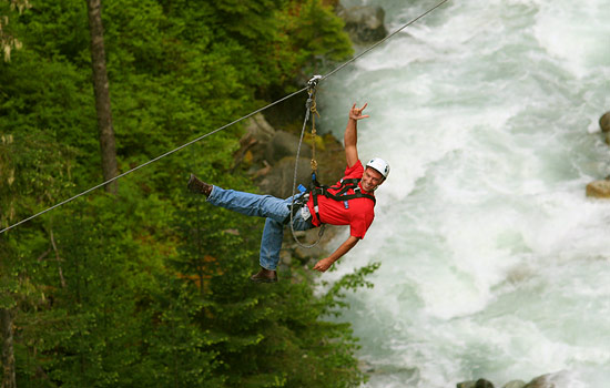 Aerial view of a man on a zip trek eco-tour over a flowing river in Whistler