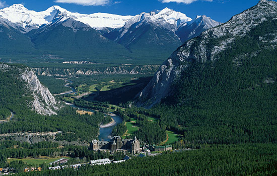 A river runs through the vast Rocky Mounatain landscape with the Banff Springs hotel at rivers edge