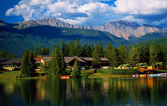 A lakeside lodge in Jasper with the the Rocky Mountains in the distance