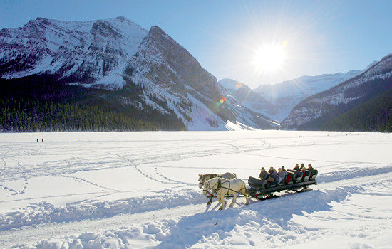 Horses pull a sleigh carrying passengers for a ride over frozen Lake Louise surrounded by the Rocky Mountains