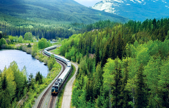 VIA Rail train travels through the Rocky mountains and lakes