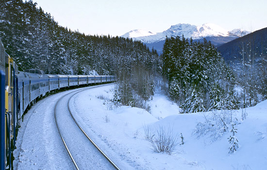 A VIA RAil train travels through a winter landscape with snowy peaks in the distance