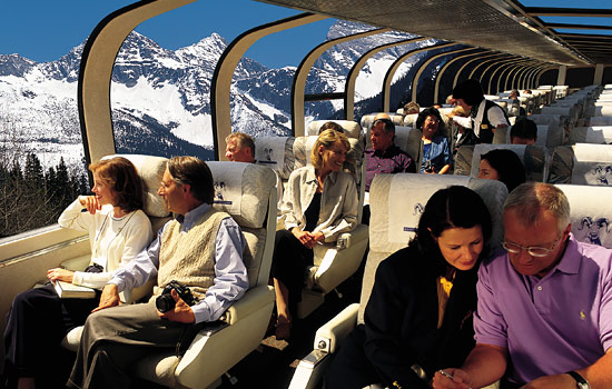 Passengers enjoy the views of the Rocky Mountains from the dome car of the Rocky Mountaineer train