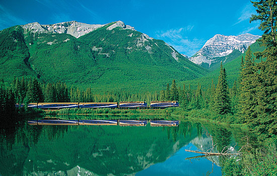 The Rocky Mountaineer passes by mountains and a lake