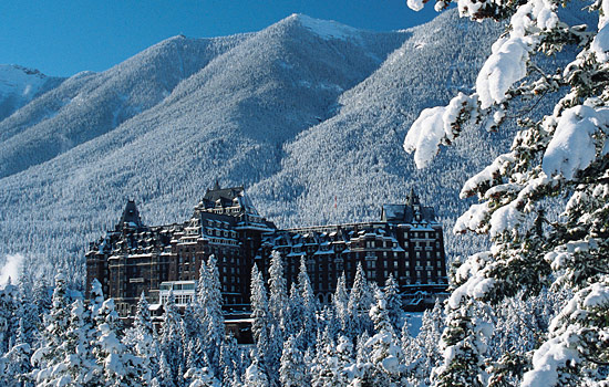 The Banff Springs hotel towers above snow covered forests at the base of the Rocky Mountains