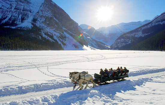 In the Rocky Mountains, visitors embark on a sleigh ride on Lake Louise