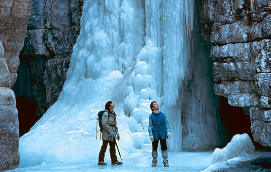 A couple on a guided tour of Maligne Canyon look up at the surrounding rocks and ice formations