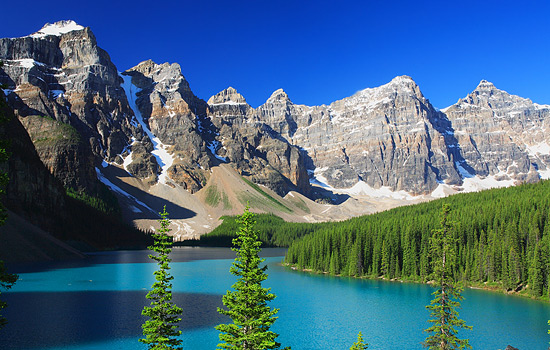 Moraine lake in the Rocky mountains is surrounded by forests and mountains
