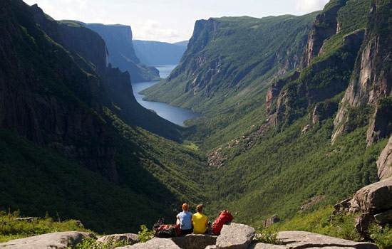 A couple sit on the rocks above a fjord in Gros Morne National Park in Newfoundland
