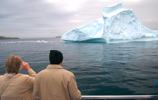 A couple look at an impressive iceberg