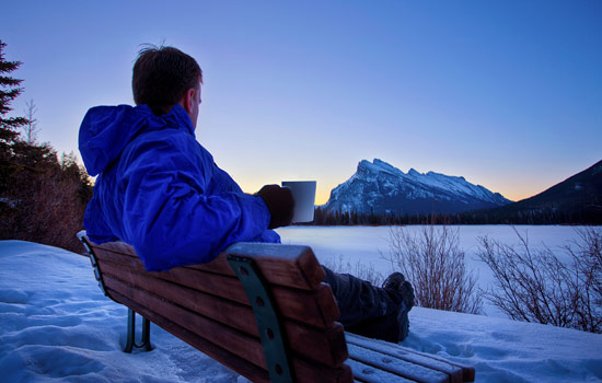 A man sits on a bench and watches the sunset behind Cascade Mountain in the distance